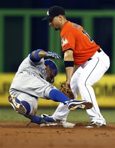 Toronto Blue Jays' Rajai Davis, left, is tagged out by Miami Marlins second baseman Omar Infante (12) during the second inning of an interleague baseball game in Miami, Sunday, June 24, 2012. (AP Photo/J Pat Carter)