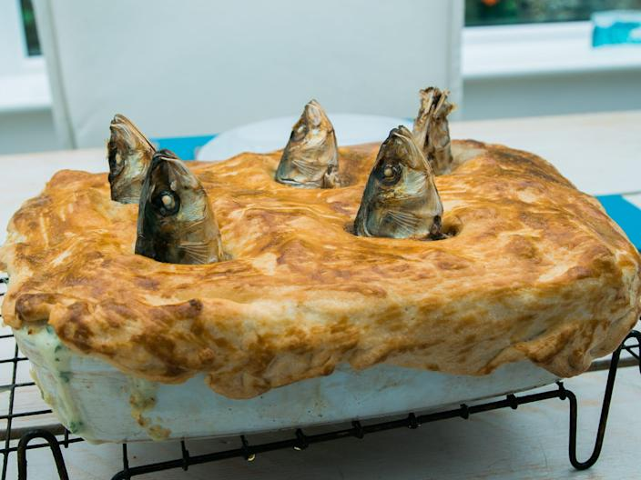 Stargazy pie with fish heads sticking out of pastry