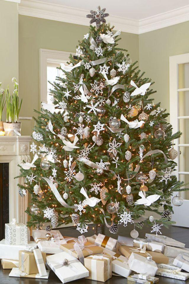 """<p>You'll be tempted to play Bing Crosby's classic Christmas tune when decorating this <a href=""""https://www.goodhousekeeping.com/holidays/christmas-ideas/g1666/christmas-party-themes-decorations/"""" rel=""""nofollow noopener"""" target=""""_blank"""" data-ylk=""""slk:frosty wonderland"""" class=""""link rapid-noclick-resp"""">frosty wonderland</a>. DIY paper doves and a pinecone topper, and fill in the gaps with snowflake ornaments and silver ribbon.  </p>"""