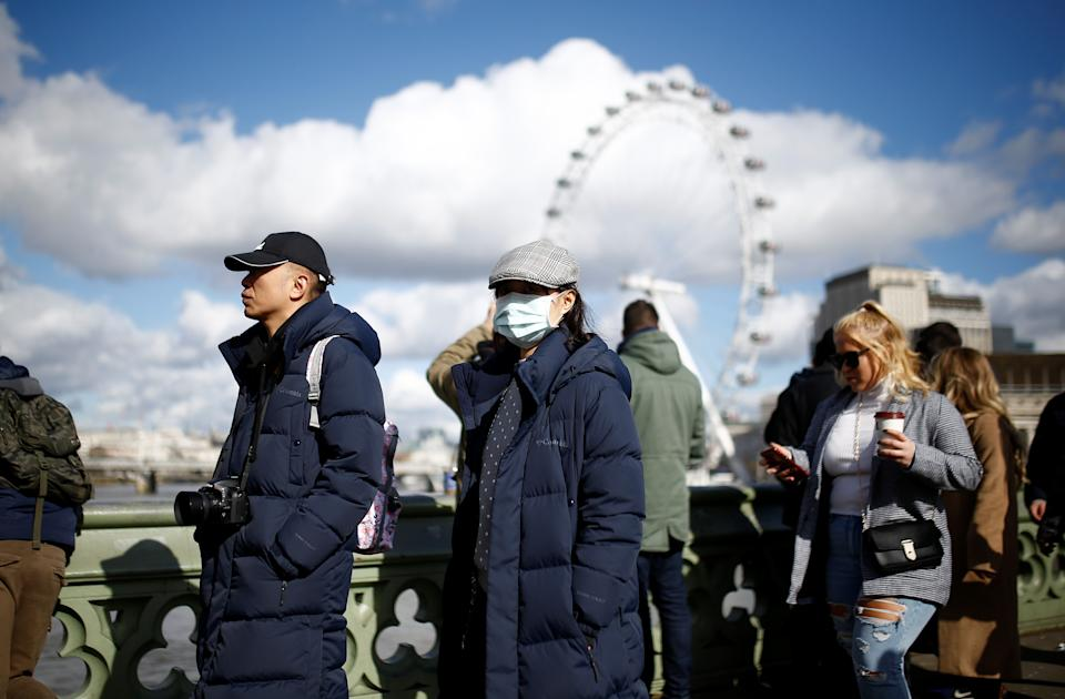 People are pictured wearing protective face masks in London, Britain, March 2, 2020. REUTERS/Henry Nicholls