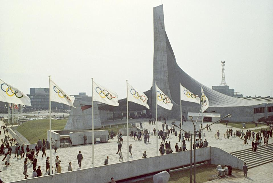 <p>Several Olympic flags fly outside Komazawa Olympic Park to signify the start of the event.</p>