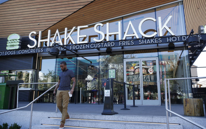 FILE - In this April 15, 2015, file photo, a man walks out of a Shake Shack in front of the New York-New York hotel and casino in Las Vegas. Shake Shack reports financial results Monday, Feb. 25, 2019. (AP Photo/John Locher, File)