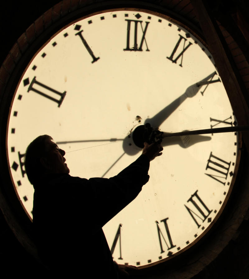 FILE - Custodian Ray Keen checks the time on a clock face after changing the time on the 97-year-old clock atop the Clay County Courthouse, in this Nov. 6, 2010 file photo taken in Clay Center, Kan. Most Americans will be able to get an extra hour of sleep Sunday Nov. 4, 2012 thanks to the annual shift back to standard time. Officially, the change occurs at 2 a.m. Sunday, but most people will set their clocks back before hitting the sack Saturday night. (AP Photo/Charlie Riedel, File)