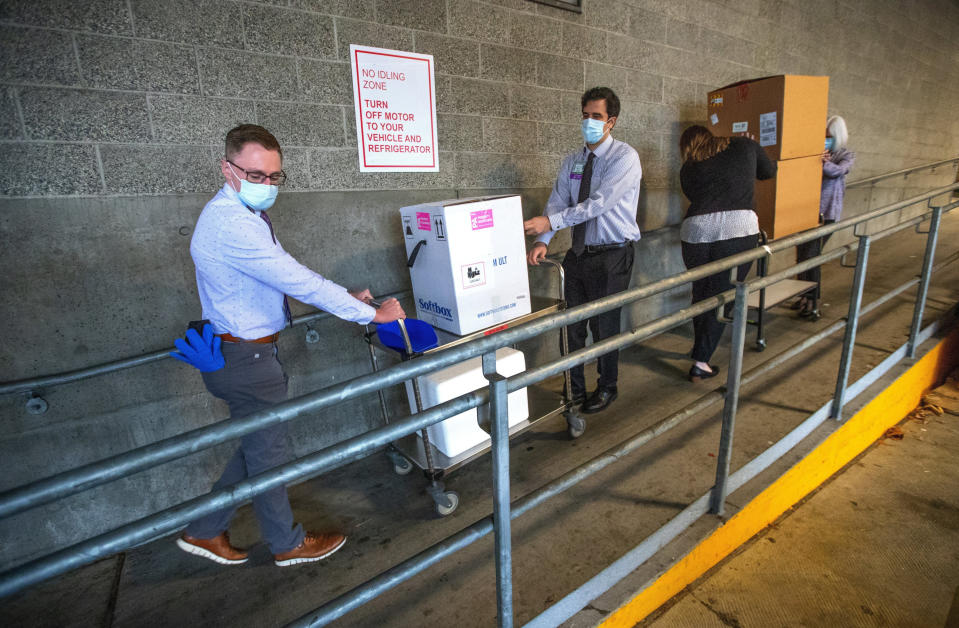 FILE - In this Dec. 14, 2020, file photo, University of Washington Medical Center Montlake campus pharmacy administration resident Derek Pohlmeyer, left, and UWMC pharmacy director Michael Alwan transport a box containing Pfizer-BioNTech COVID-19 vaccines toward a waiting vehicle headed to the UW Medical Center's other hospital campuses in Seattle. (Mike Siegel/The Seattle Times via AP, Pool, File)
