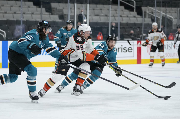 Anaheim Ducks center Sam Carrick (39) moves the puck up the ice past San Jose Sharks' Erik Karlsson (65) and Jeffrey Truchon-Viel (63) during the second period of an NHL hockey game, Monday, April 12, 2021, in San Jose, Calif. (AP Photo/Tony Avelar)