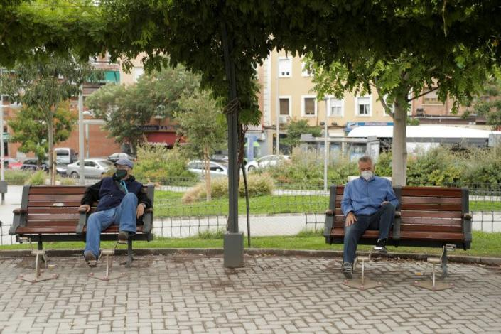 People wearing protective face masks sit at benches at Carabanchel neighbourhood in Madrid