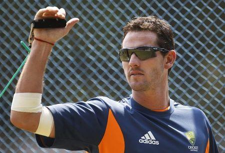 Australia's Tait performs a stretching exercise during a cricket practice session in Bangalore