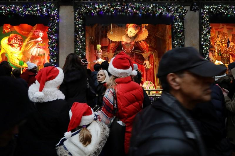 People wearing Christmas hats look in a shop window on Fifth Avenue during a busy shopping day in Manhattan