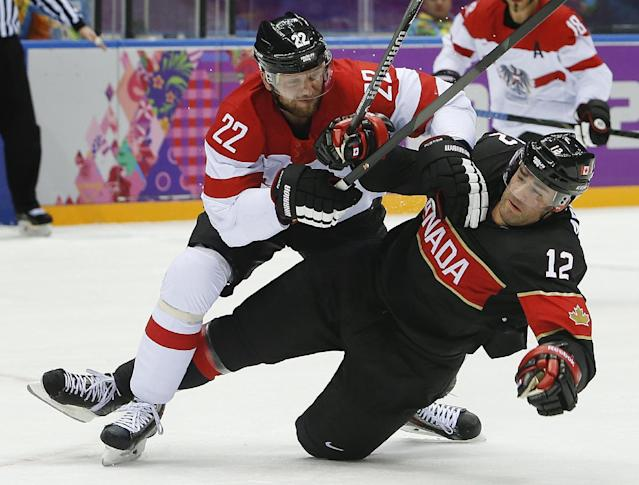 Austria defenseman Thomas Pock collides with Canada forward Patrick Marleau in the first period of a men's ice hockey game at the 2014 Winter Olympics, Friday, Feb. 14, 2014, in Sochi, Russia. (AP Photo/Mark Humphrey)
