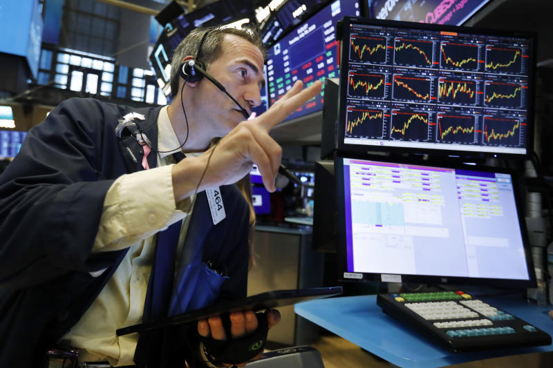 FILE - In this July 30, 2019 file photo, trader Gregory Rowe works on the floor of the New York Stock Exchange. An economic alarm bell is sounding in the U.S. and sending warnings of a potential recession.