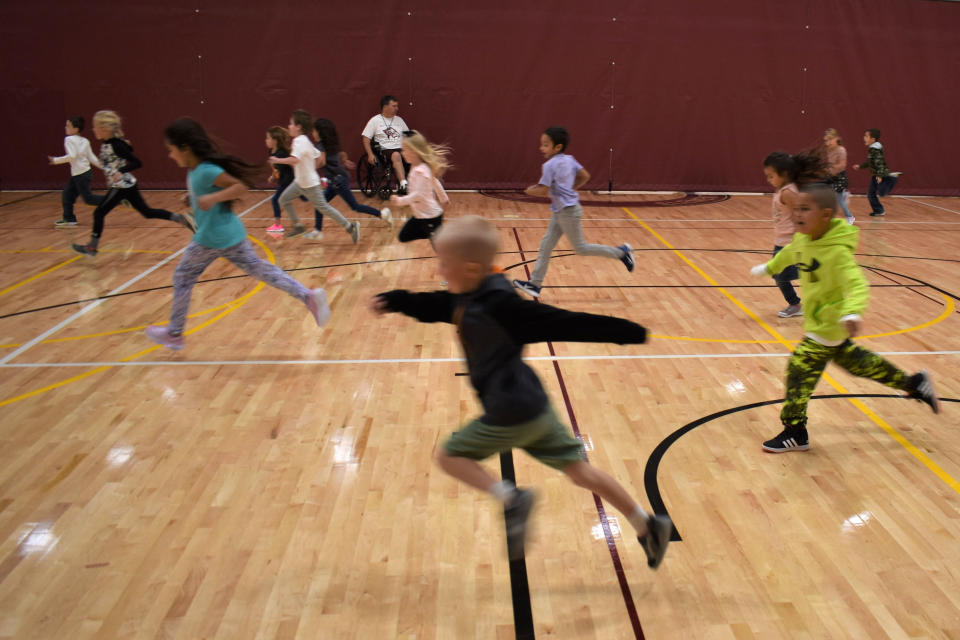Students in the first grade run through a gymnasium at Fox Hills Elementary School, Aug. 26, 2021, in Watford City, N.D., part of McKenzie County. School enrollment tripled over the past decade and is expected to double again by 2030, as McKenzie County became the fastest growing county in the U.S. (AP Photo/Matthew Brown)