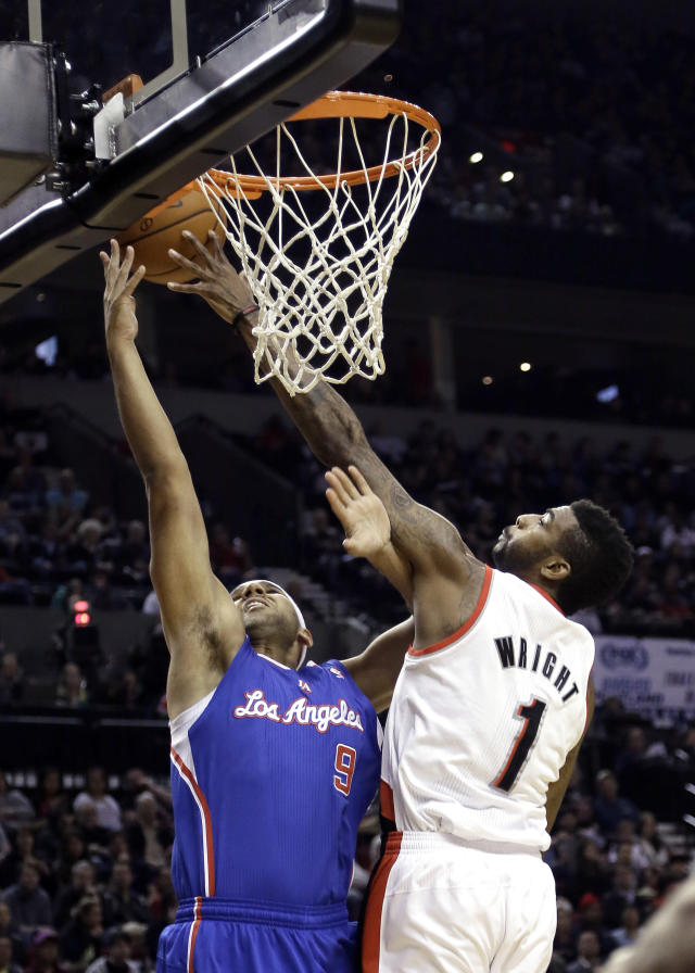 Portland Trail Blazers forward Dorell Wright, right, blocks a shot by Los Angeles Clippers forward Jared Dudley during the first half of an NBA basketball game in Portland, Ore., Wednesday, April 16, 2014. (AP Photo/Don Ryan)
