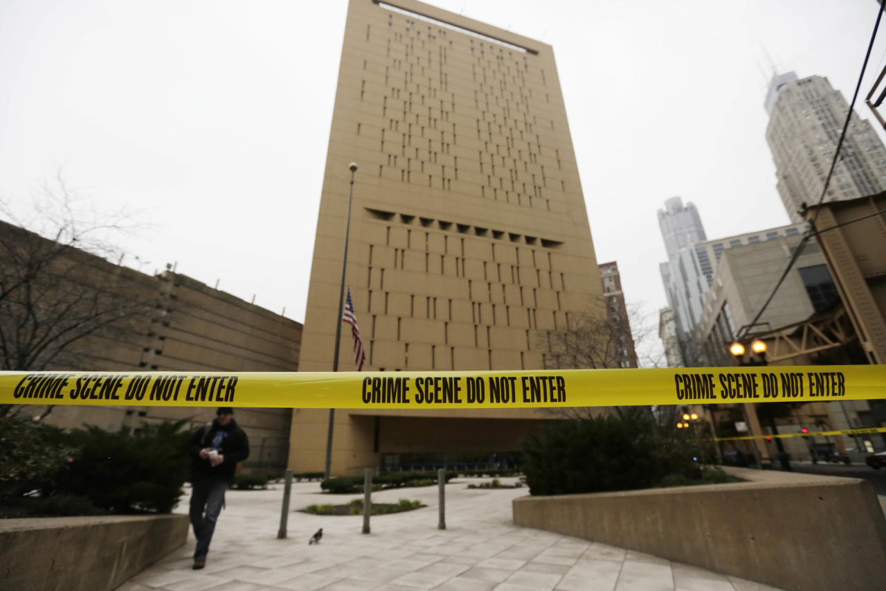 Police tape surrounds the Metropolitan Correctional Center Tuesday, Dec. 18, 2012, in Chicago. Two convicted bank robbers used a knotted rope or bed sheets to escape from the federal prison window high above downtown Chicago early Tuesday, a week after one of them made a courtroom vow of retribution, to federal judge. The escape occurred sometime between 5 a.m. and 8:45 a.m. when the inmates were discovered missing, Chicago Police Sgt. Mark Lazarro said. Hours later, what appeared to be a rope, knotted at six-foot intervals, could be seen dangling into an alley from a window of the Metropolitan Correctional Center approximately 20 stories above the ground. (AP Photo/M. Spencer Green)