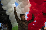 A supporter of Syrian President Bashar Assad prepares to release hundreds of balloons with the colors of the Syrian flag at a gathering at Omayyid Square in the Syrian capital Damascus, Syria, Sunday, May 23, 2021. The presidential elections in the war-ravaged country was held on May 26. (AP Photo/Hassan Ammar)