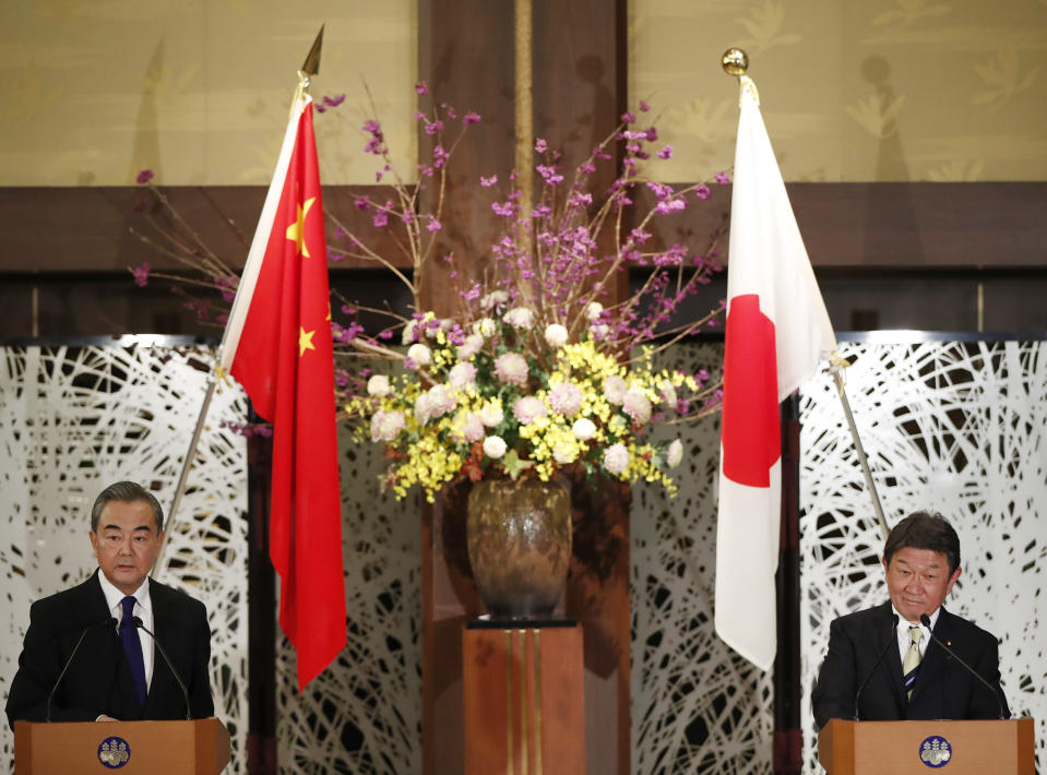 China' Foreign Minister Wang Yi, left, and his Japanese counterpart Toshimitsu Motegi participate in a press briefing in Tokyo on Tuesday, Nov. 24, 2020. Wang met Motegi on Tuesday to discuss ways to revive their pandemic-hit economies as well as regional concerns over China's growing influence. (Issei Kato/Pool Photo via AP)