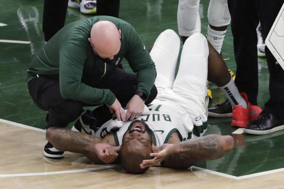 Milwaukee Bucks' P.J. Tucker is checked on by a trainer after suffering an injury during the second half of the team's NBA basketball game against the Washington Wizards on Wednesday, May 5, 2021, in Milwaukee. (AP Photo/Aaron Gash)