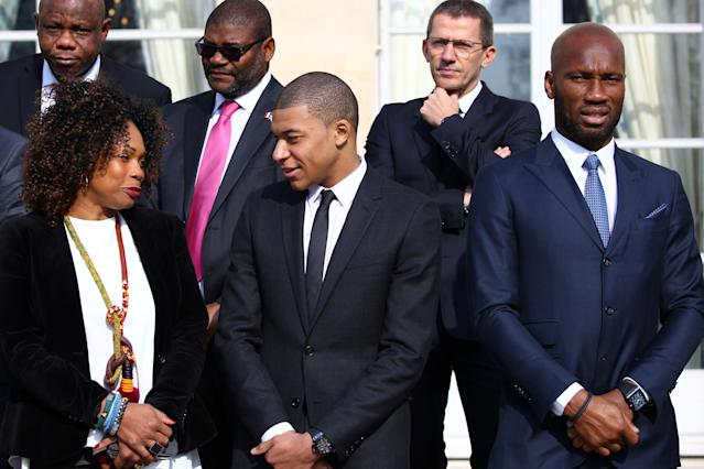 Paris Saint-Germain's soccer player Kylian Mbappe, former soccer player Didier Drogba and guests react after a family picture with French President Emmanuel Macron, Liberian President George Weah and his wife Clar before a lunch at the Elysee Palace in Paris, France, February 21, 2018. REUTERS/Stephane Mahe