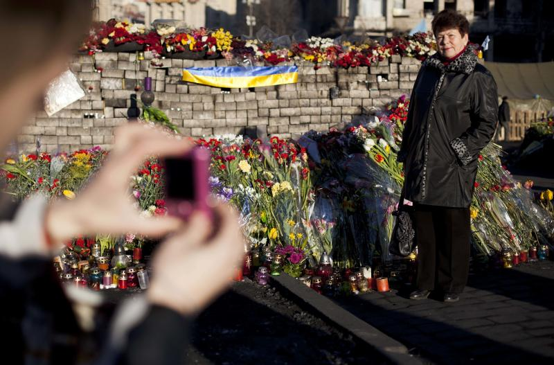 A woman poses for a photograph next to a wall composed of paving stones and adorned with flowers and candles placed in memory of those who died in clashes which took place in late February in Kiev's Independence Square, Ukraine, Tuesday, March 11, 2014. (AP Photo/David Azia)