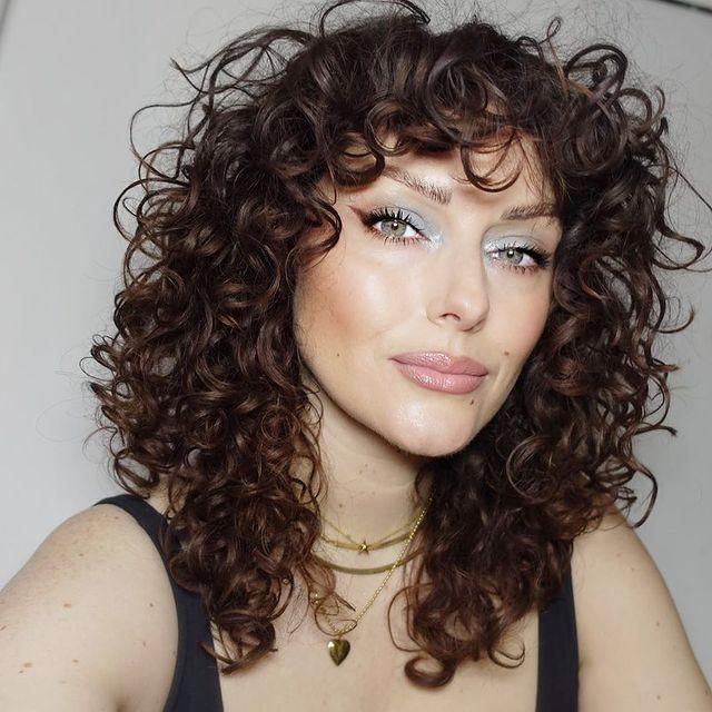 "<p>Curly bangs bring the attention up to your eyes, so don't be afraid to play with colorful and metallic shadows like makeup artist Katie Jane Hughes.</p><p><a href=""https://www.instagram.com/p/CHEABnzjU_x/"" rel=""nofollow noopener"" target=""_blank"" data-ylk=""slk:See the original post on Instagram"" class=""link rapid-noclick-resp"">See the original post on Instagram</a></p>"
