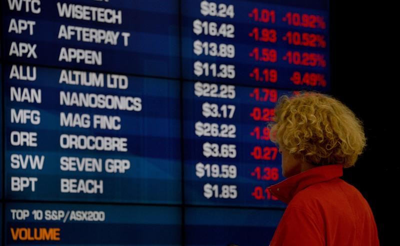 A visitor to the Australian Securities Exchange (ASX) looks at share prices on a big screen in Sydney on October 11, 2018. - The Australian share market joined the regional bloodbath after the sell off on Wall Street, plunging to a more than five-month low as all sectors dropped into the red. (Photo by PETER PARKS / AFP) (Photo credit should read PETER PARKS/AFP via Getty Images)