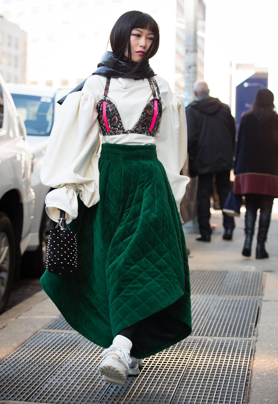<p>A guest walks outside the Son Jung Wang show wearing a black scarf, white shirt, green dress and white shoes. <em>[Photo: Getty]</em> </p>