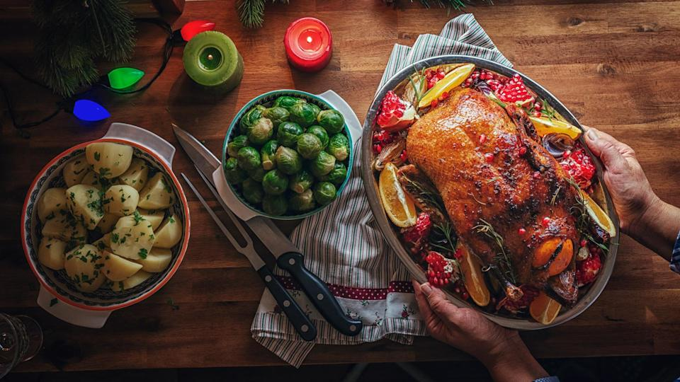Traditional Christmas Duck Holiday Dinner with Oranges, Pomegranate, Potatoes and Brussels Sprout.