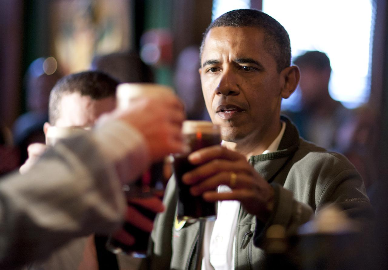 WASHINGTON, DC - MARCH 17:  (AFP OUT) U.S. President Barack Obama toasts with Guinness beer as he visits a bar in celebration of St. Patrick's day at the Dubliner Restaurant and Pub on March 17, 2012 in Washington, DC. Next week, Obama and Vice President Biden will meet the Irish Prime Minister Enda Kenny and attend a St. Patrick's Day lunch at the Capitol. (Photo by Joshua Roberts/Getty Images)
