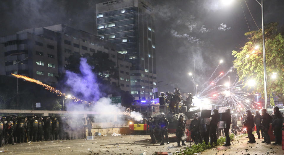 Indonesian riot police fire tear gas to disperse student protesters during a clash outside parliament in Jakarta, Indonesia, Tuesday, Sept. 24, 2019. Police fired tear gas and water cannons Tuesday to disperse thousands of rock-throwing students protesting a new law that they said has crippled Indonesia's anti-corruption agency. (AP Photo/Achmad Ibrahim)