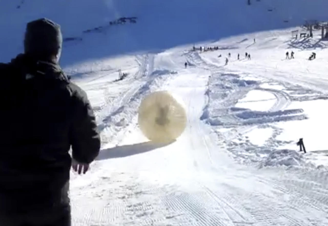 CORRECTING RESORT LOCATION TO DOMBAI - In this frame grab made Wednesday Jan. 9, 2013, taken from APTN video provided by Yekaterina Achkasova, as her husband Denis Burakov and another man are seen inside a large plastic ball called a zorb, on Thursday, Jan. 3, 2013, as they roll down a hill beore tragedy struck at the winter sports venue at Dombai in the Caucasus Mountains of southern Russia. What was supposed to be a thrilling ride down a ski slope inside a giant inflatable ball has ended in tragedy when the zorb veered off course and sailed over a cliff, killing Denis Burakov and leaving the other man badly injured. (AP Photo/Family photo provided by Yekaterina Achkasova, APTN)