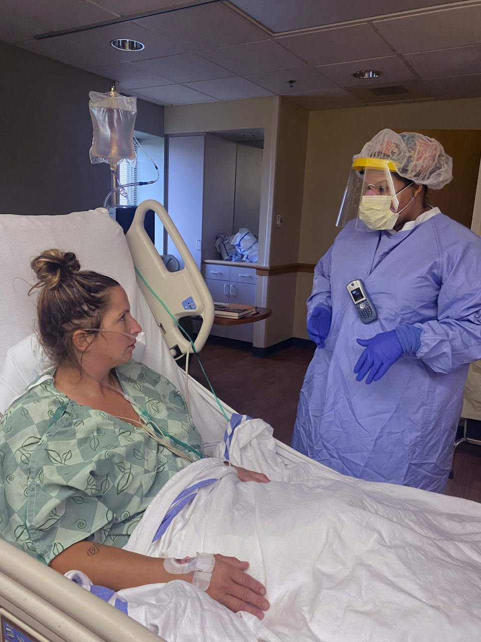 In this photo provided by Ascension Via Christi Health System, Jenifer Phelps, right, a nurse manager, talks with patient Angie Mooneyham in an intensive care unit for coronavirus patients at the Ascension Via Christi St. Francis hospital, Friday, Aug. 7, 2020 in Wichita, Kan. The hospital has created two new units for coronavirus patients as hospitalizations have increased, both in Wichita and across Kansas. (Ascension Via Christi Health System via AP)