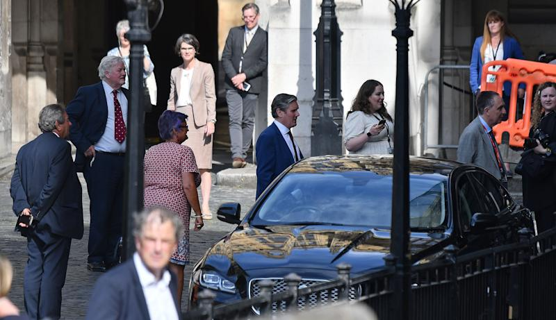 Britain's main opposition Labour Party leader Keir Starmer (C) and other MPS are pictured queuing in a courtyard on the parliamentary estate to vote on the motion of 'Proceedings during the pandemic', in the socially-distanced House of Commons in London on June 2, 2020, relating to voting procedure during the novel coronavirus COVID-19 pandemic. - Hundreds of MPs formed a lengthy physical queued to vote on the motion to abandon remote voting and use a new system where the MPs form a predetermined queue and slowly file through the lower elected parliamentary chamber to cast their ballots while keeping apart to avoid the spread of COVID-19. (Photo by JUSTIN TALLIS / AFP) (Photo by JUSTIN TALLIS/AFP via Getty Images)