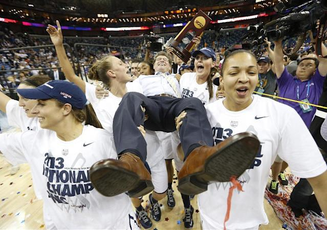 FILE - In this April 9, 2013, file photo, Connecticut players celebrate as they carry their head coach Geno Auriemma after defeating Louisville 93-60 in the national championship game of the women's Final Four of the NCAA college basketball tournament in New Orleans. The photo was honored by the Associated Press Sports Editors as best sports feature photo of 2013 at their annual winter meeting in Indianapolis. (AP Photo/Dave Martin, File)