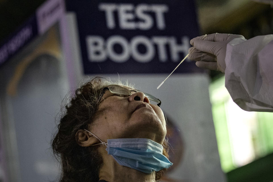 A medical worker conducts a COVID-19 swab test on a resident at a basketball court on August 6, 2020 in Navotas City, Metro Manila, Philippines. (Photo by Ezra Acayan/Getty Images)