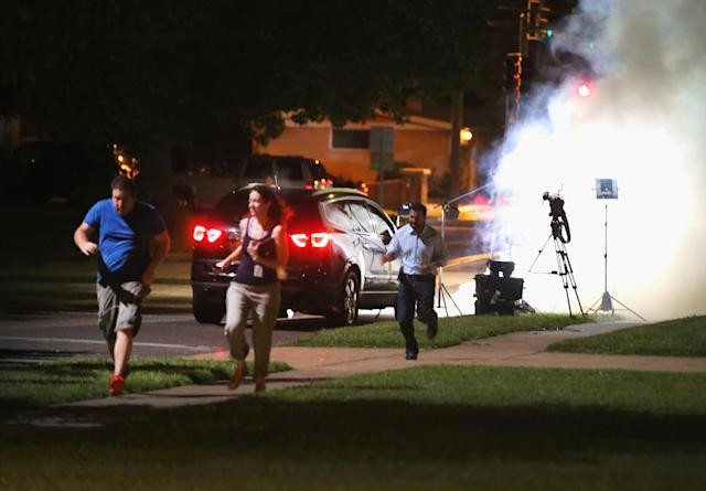 <p>An Al Jazeera television crew, covering demonstrators protesting the shooting death of teenager Michael Brown, scramble for cover as police fire tear gas into their reporting position on August 13, 2014 in Ferguson, Missouri. Brown was shot and killed by a Ferguson police officer on Saturday. Ferguson, a St. Louis suburb, is experiencing its fourth day of violent protests since the killing. (Scott Olson/Getty Images) </p>