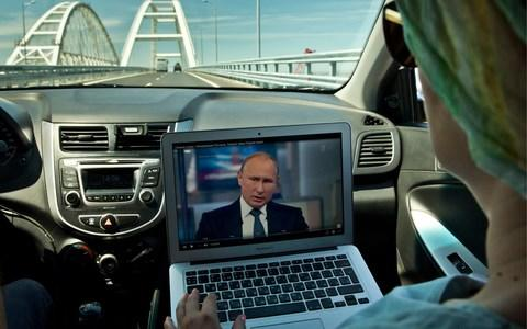 Russians watch Mr Putin's question-and-answer session while driving over a new bridge to Crimea, which was covered at length during the show - Credit: Sergei Malgavko/TASS via Getty Images
