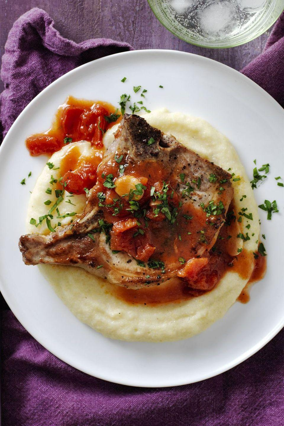 """<p>If you're looking for a hearty, savory dish that you can put together in almost no time at all, this pork chop should be your go-to.</p><p><em><a href=""""https://www.womansday.com/food-recipes/recipes/a57909/pork-chops-parmesan-polenta-recipe/"""" rel=""""nofollow noopener"""" target=""""_blank"""" data-ylk=""""slk:Get the Pork Chops and Garlicky Tomatoes with Parmesan Polenta recipe."""" class=""""link rapid-noclick-resp"""">Get the Pork Chops and Garlicky Tomatoes with Parmesan Polenta recipe.</a></em></p>"""