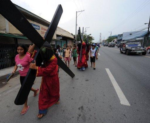 Penitents carry crosses on the eve of the Good Friday reenactments of the crucifixion of Jesus Christ in San Fernando City, Pampanga province, north of Manila, on April 5. Despite the church advice to shun the practice, devout Filipinos self-flagellate as others prepare to get nailed to crosses as Asia's bastion of Catholicism gets set to mark Good Friday