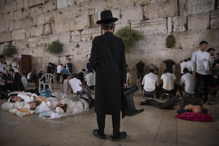 Ultra-Orthodox Jewish men pray as others sleeping during the mourning ritual of Tisha B'Av (Ninth of Av) fasting and a memorial day, commemorating the destruction of ancient Jerusalem temples, at the Western Wall, the holiest site where Jews can pray in the Old City of Jerusalem, Sunday, July 18, 2021. (AP Photo/Oded Balilty)