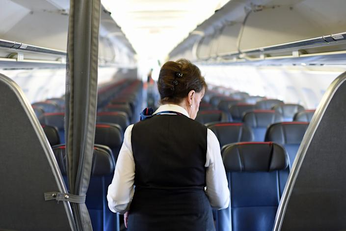An American Airlines flight attendant checking the passengers' seats for forgotten items before disembarking from her flight to Boston at Ronald Reagan Washington Airport in Arlington, Virginia.