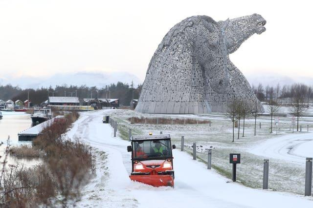 A staff member uses a vehicle to clear snow on a pathway at the Kelpies, near Falkirk in Scotland