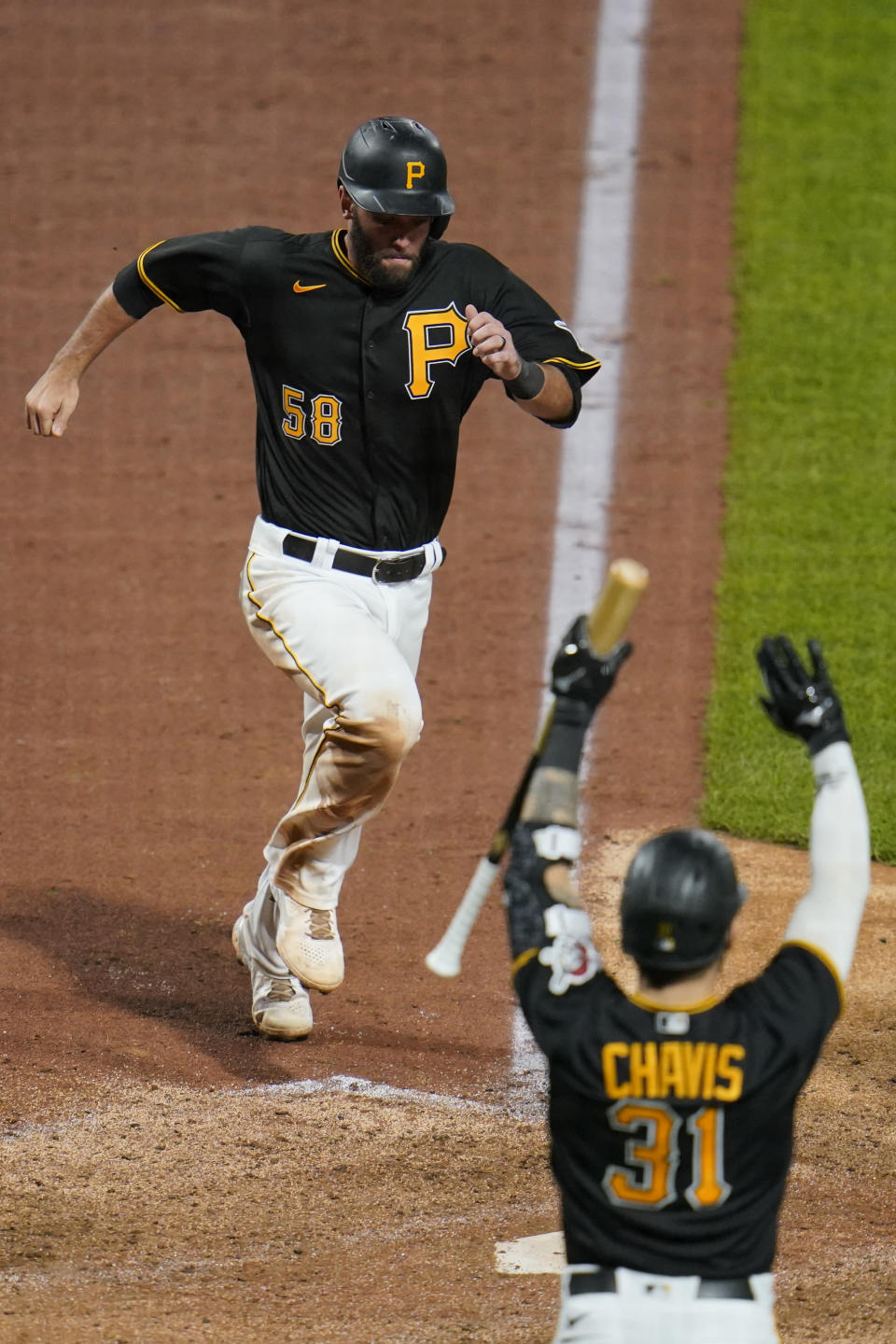 Pittsburgh Pirates' Jacob Stallings (58) scores the second of two runs on a tripe by Hoy Park off Chicago Cubs relief pitcher Adam Morgan during the sixth inning of a baseball game in Pittsburgh, Tuesday, Sept. 28, 2021. (AP Photo/Gene J. Puskar)