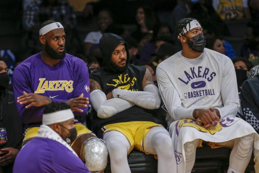 Los Angeles Lakers forwards LeBron James (6), Carmelo Anthony (7) and Anthony Davis (3) watch on the bench during the second half of a preseason NBA basketball game against the Golden State Warriors in Los Angeles, Tuesday, Oct. 12, 2021. (AP Photo/Ringo H.W. Chiu)