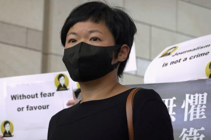 Journalist Bao Choy poses for pictures outside West Kowloon Magistrates' Courts in Hong Kong