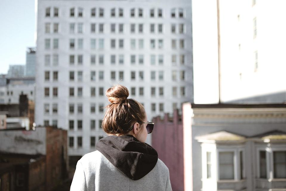 Young adult woman with her hair in a bun wearing sunglasses in front of urban buildings from a rooftop