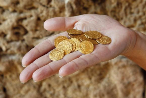 An Israel Nature and Parks Authority employee displays gold coins found hidden in a ceramic jug at the Arsuf cliff-top coastal ruins, 15 km (9 miles) from Tel Aviv July 9, 2012. The 1,000-year-old treasure was unearthed at the famous Crusader battleground where Christian and Muslim forces once fought for control of the Holy Land.