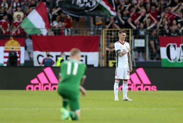 Hungary's Bendeguz Bolla stands while Republic of Ireland midfielder James McClean takes a knee at the Szusza Ferenc Stadium in Budapest