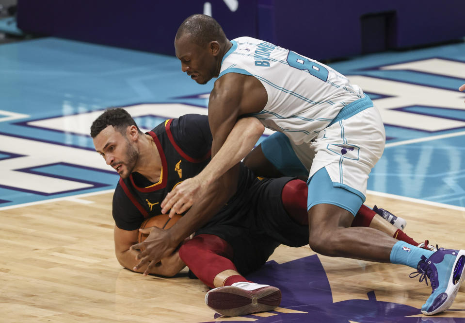Charlotte Hornets center Bismack Biyombo, right, and Cleveland Cavaliers forward Larry Nance Jr. (22) vie for the ball during the second quarter of an NBA basketball game in Charlotte, N.C., Wednesday, April 14, 2021. (AP Photo/Nell Redmond)