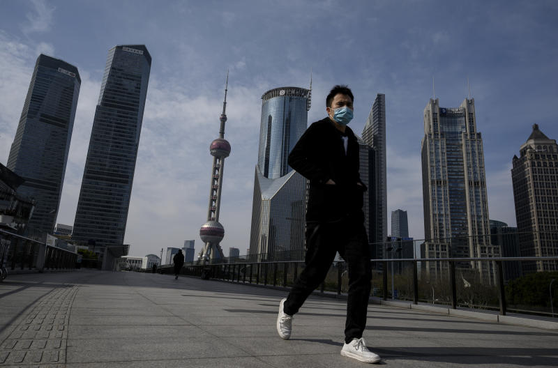 A man wearing a protective face mask walks on an overpass in Lujiazui financial district in Shanghai on February 10, 2020. - The death toll from the novel coronavirus surged past 900 in mainland China on February 10, overtaking global fatalities in the 2002-03 SARS epidemic, even as the World Health Organization said the outbreak appeared to be stabilising. (Photo by NOEL CELIS / AFP) (Photo by NOEL CELIS/AFP via Getty Images)