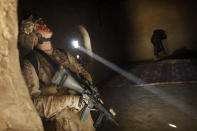 """United States Marine LCpl. Franklin Romans of Michigan, from the 2nd Battalion 2nd Marines """"Warlords"""" searches a house during an operation in the Garmsir district of the volatile Helmand province, southern Afghanistan, on Dec. 23, 2009. (AP Photo/Kevin Frayer, File)"""