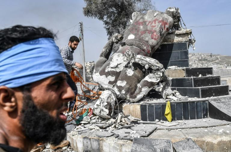 Turkish-backed Syrian rebels remove a rope from the statue of Kurdish hero Kawa after destroying it in the city of Afrin in northern Syria on March 18, 2018